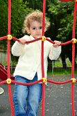 Young child playing on a rope ladder climbing frame.