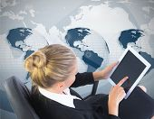 Composite image of businesswoman sitting on swivel chair with tablet on global background