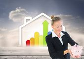 Composite image of blonde businesswoman holding piggy bank in front of house containing statistic