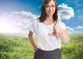 Composite image of attractive businesswoman looking and pointing at camera standing on grass