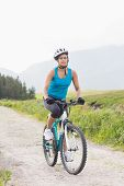 Fit woman riding mountain bike on a country trail