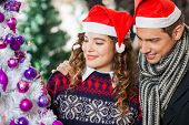 Happy young couple looking at decorated Christmas tree at store