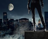 image of superhero  - Sexy Female thief with gun new york on background - JPG