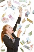 Happy lucky business woman catching flying Euro money banknotes