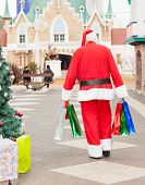Rear view of Santa Claus with bags walking in courtyard