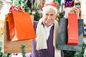 Portrait of happy senior man in Santa hat carrying shopping bags at Christmas store