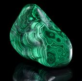 Polished malachite stone close up  with reflection on black surface background
