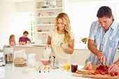 Parents Preparing Family Breakfast In Kitchen