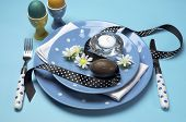 Happy Easter Dinner Table Setting With Blue Polka Dot Plates, And Decorations Against A Blue Backgro