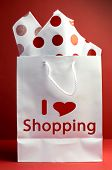 I Love Shopping Concept With White Bag And Red Polka Dot Tissue Paper Against A Red Background, Vert