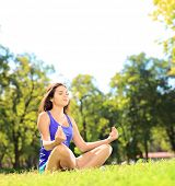 Young female athlete in sportswear meditating seated on a green grass in a park, shot with a tilt and shift lens