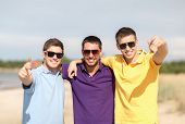 summer, holidays, vacation, happy people concept - group of friends having fun on the beach and pointing at you
