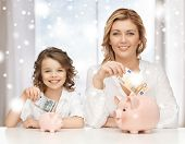 banking, finances, investment and happy people concept - mother and daughter with piggy banks and pa