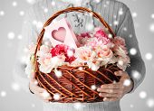 valentine's day, christmas, x-mas, winter, happiness concept - man holding basket full of flowers and postcard