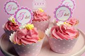 Pink Wedding Cupcakes With I Do Topper Signs On Pink Cake Stand - Close Up.