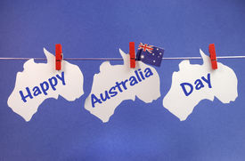 picture of pegging  - Celebrate Australia Day holiday on January 26 with a Happy Australia Day message greeting written across white Australia and flag hanging pegs on a line against a blue background - JPG
