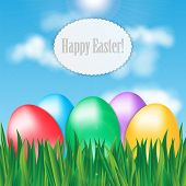 Colorful Easter Eggs On Green Grass On Blue Sky Background And Frame For Your Text
