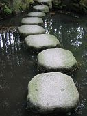 stock photo of stepping stones  - stepping stones over pond - JPG