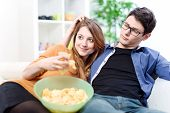 Beautiful Young Couple Watching Tv And Eating On A Sofa