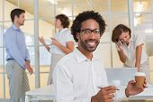 Portrait of a smiling young businessman holding disposable coffee cup with colleagues in background at office