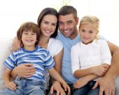 image of happy family  - Happy young family sitting on sofa at home - JPG