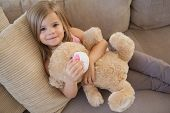 High angle portrait of a young smiling girl with stuffed toy sitting on sofa in the living room at h
