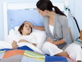 Madre de tomarle la temperatura a su hijo