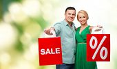 happiness, shopping and couple concept - smiling couple with shopping bags with sale and percent sign