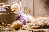 stock photo of wooden basket  - Colorful easter eggs in a basket on a wooden background - JPG