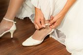 Fragment Of Woman's Arm And Hands Fastening White Wedding Shoes.