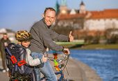 Father With Son Riding By Bicycle Along The River Waterfront In Krakow