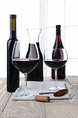 High key wine still life. Vertical format on a farmhouse style table with a white background with wi