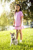 Young asian Girl walking Welpe angeleint auf Gras