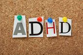 foto of attention  - ADHD the abbreviation for Attention Deficit Hyperactivity Disorder in cut out magazine letters pinned to a cork notice board - JPG