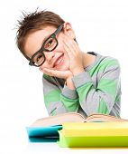 Cute little boy is reading a book while wearing glasses supporting his head with both hands, isolated over white