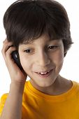 Eight year old boy with mobile phone on white background
