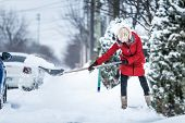 stock photo of shovel  - Woman Shoveling her Parking Lot after a Snowstorm - JPG
