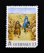 a stamp printed in the Guernsey that shows the biblical scene of Jesus Flight into Egypt