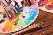Artistic equipment: paint, brushes and art palette on wooden table
