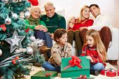 Happy children opening gifts at christmas while parents and grandparents are watching