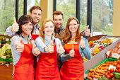 Happy supermarket staff team holding thumbs up in teamwork effort