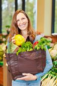 Smiling woman shopping for vegetables in a supermarket