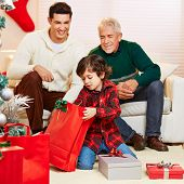 Happy boy opening gifts at christmas and father and grandfather watching