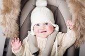 Funny Little Baby In A Warm Hat Sitting In A Stroller