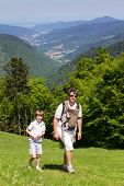 Father With Son And Newborn Daughter In A Baby Carrier Hiking In The Mountains