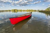 red canoe on a calm lake in a fisheye perspective, late summer in Fort Collins, Colorado