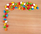 Border Frame of Colorful  JellyBeans Candies spilled on surface wooden table. top view