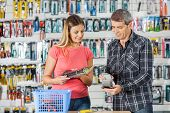 Man and woman making electronic payment in hardware store