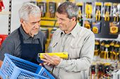 Senior salesman assisting customer in buying product at hardware store