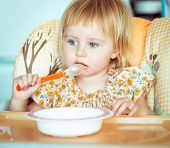 cute baby girl is holding a spoon and going to eat